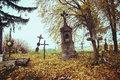Scary leaning cross tomb stones in a foggy autumn scene in fall. Old creepy graves on cemetery in Slovakia. Spooky aged tombstones Royalty Free Stock Photo