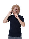 Scary man talking to the phone with a finger on his mouth Royalty Free Stock Image