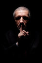 Scary mature man gesturing silence black background Stock Photography