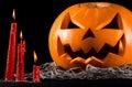 Scary pumpkin, jack lantern, pumpkin halloween, red candles on a black background, halloween theme, pumpkin killer Royalty Free Stock Photo