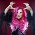 Scary witch with red hair performs magic on a pink background. Halloween, horror theme. Royalty Free Stock Photo