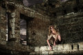 Scary woman in the ruins fantasy style portrait of sitting on ruined wall Stock Image