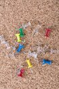 Scattered pile of multicolored thumb tacks on a brown cork board Royalty Free Stock Photo