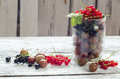 Scattered small organic fruit, red, black currant and gooseberries on a wooden table Royalty Free Stock Photo