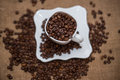A scattering of coffee beans white cup and saucer on table brown texture units large lot grain Royalty Free Stock Photos