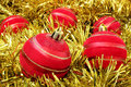 A scattering of red christmas balls on fluffy golden garland Stock Images