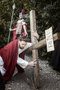 Scene of Jesus life. Unidentified man portraying Jesus Christ carries large wooden cross during reenactment of the Crucifixion
