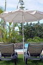 Scene with swimming pool.Two deck chairs under umbrella. Canary Islands. Spain. Royalty Free Stock Photo