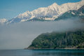 Scene was taken departing whittier alaska boat features fog forest snow capped mountains sea Stock Photo
