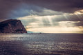 Scenic landscape with cliff rock at sea during sunset with sun rays breaking through dramatic clouds  during sunset and copy space Royalty Free Stock Photo