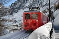 Scenic mountain train in snow small red climbing railway the Royalty Free Stock Images
