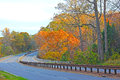 Scenic part of city highway during sunset hours in fall motorists travel on the road along the thicket autumn colorful foliage Stock Photo