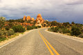 Scenic road through arches national park utah usa red rock formations and storm clouds Stock Image