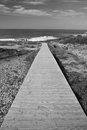 Scenic seascape empty wooden pathway leading to atlantic ocean with waves Royalty Free Stock Photo