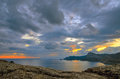 Scenic sky at sunset over the bay in sudak on the black sea in crimea panorama of of golden many clouds rocky crimean mountains Royalty Free Stock Photos