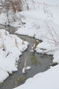 Scenic view of creek or stream receding through snowy countryside Stock Images