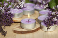 Scented candles on a wooden stand with lilac flowers the table Royalty Free Stock Photos