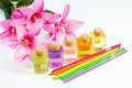 Scented oil studio shot of bottles of multi colored reed diffuser and pink flowers Royalty Free Stock Photography