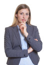 Sceptical blonde businesswoman in a grey blazer on an white background for cut out Royalty Free Stock Photography