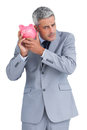 Sceptical businessman holding piggy bank on white background Royalty Free Stock Photos