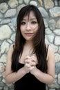 Schönes asiatisches Mädchen mit den Händen umklammert Stockfotografie