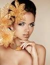 Schönes mädchen mit goldenen blumen schönheit vorbildliches woman face pro Lizenzfreie Stockfotografie
