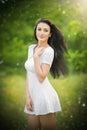 Schöne junge frau die in einer sommerwiese aufwirft porträt des attraktiven brunettemädchens mit dem langen haar das in der Stockfotos