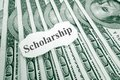 Scholarship money text on paper over hundred dollar bills Royalty Free Stock Photo