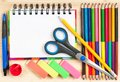 School accessories colorful pencils with notepad and over wooden surface Royalty Free Stock Photo
