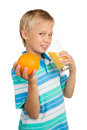 School aged boy holds a glass with an orange juice with one hand is holding in and in another Royalty Free Stock Image
