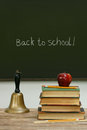 School bell and books on desk with chalkboard in background Royalty Free Stock Images