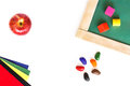 School board, colored blocks, red apple, wax crayons, colored paper lying on a white wooden background. Royalty Free Stock Photo