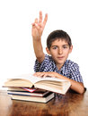 School boy with arm up answering young little books on table hand waiting for teacher attention isolated on white Stock Photo
