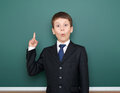 School boy in black suit show finger up gesture and wonder, point on green chalkboard background, education concept Royalty Free Stock Photo