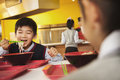 School boy eats noodles in school cafeteria Stock Image