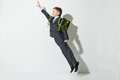 School boy flying over grey background Royalty Free Stock Photo