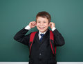 School boy make faces in black suit on green chalkboard background with red backpack, education concept Royalty Free Stock Photo