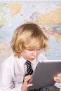 School boy working hard on a pc tablet concentrating with the world map in the background Royalty Free Stock Photo