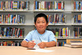 School Boy Working on Homework at Library Royalty Free Stock Photo