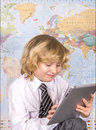 School boy working on a pc tablet happily with the world map in the background Royalty Free Stock Images