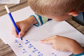 School boy writing on paper writing the alphabet with pencil kid homework education concept Royalty Free Stock Images