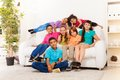 School boys and girls at home together close portrait of group of seven kids of age sitting in living room Royalty Free Stock Images