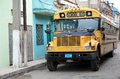 School bus a cuban man is driving a typical old classic north amrican along the street in santa clara cuba Royalty Free Stock Photos