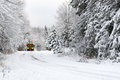School bus drives on snow covered rural road a down a country lined with trees after a storm during the winter Stock Photography