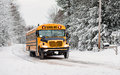 School Bus Driving Down A Snow Covered Rural Road - 3 Royalty Free Stock Photo