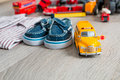 School bus toy near shirts and blue boat shoes on grey wooden background. Boy outfit. Close up. Royalty Free Stock Photo
