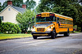 School bus yellow driving along street Stock Images