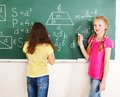 School child writting on blackboard. Royalty Free Stock Photo