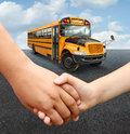 School children bus with two young students of elementary age holding hands preparing to go into the yellow transport vehicle as Stock Photos