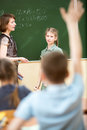 School children in classroom at math lesson kids with raised hands Stock Image